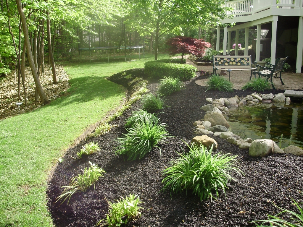 Landscaping including pond and mulched bed with plants